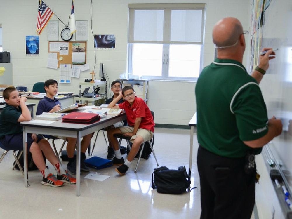 Students watching teacher write on board