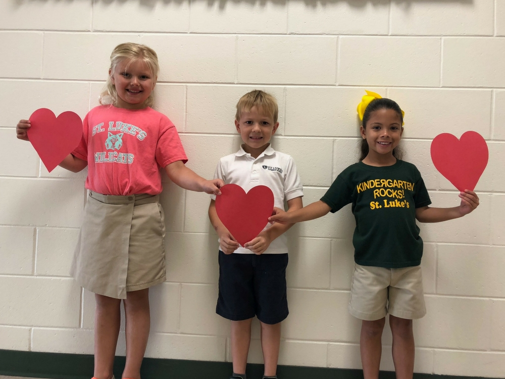 Students smiling while holding hearts