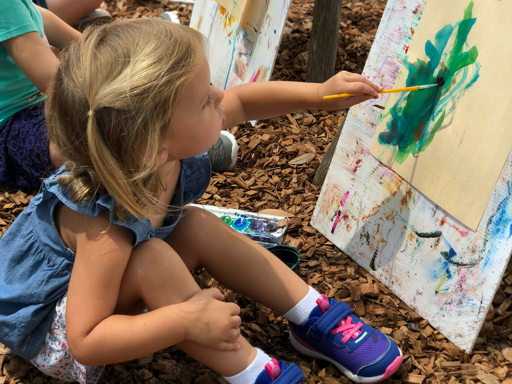 Little girl painting outside