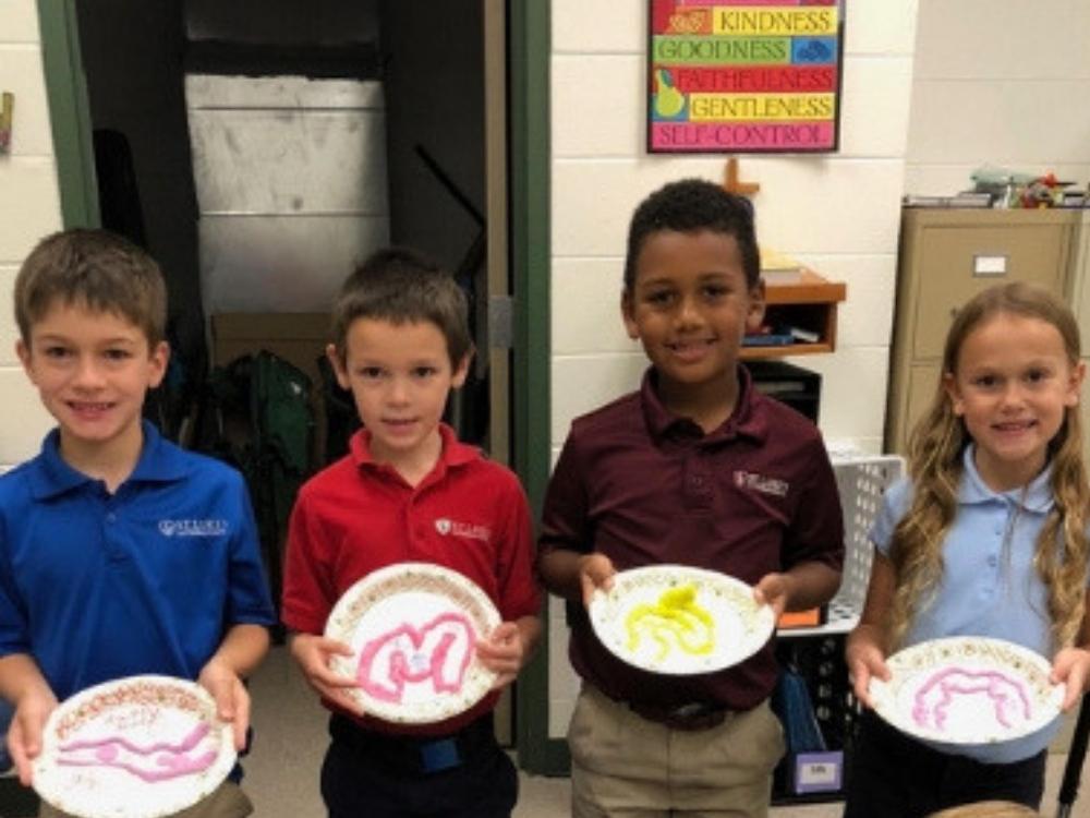 Four children holding art