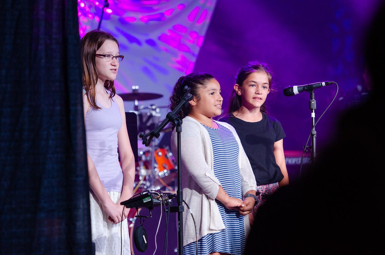 Three Children Singing on Stage