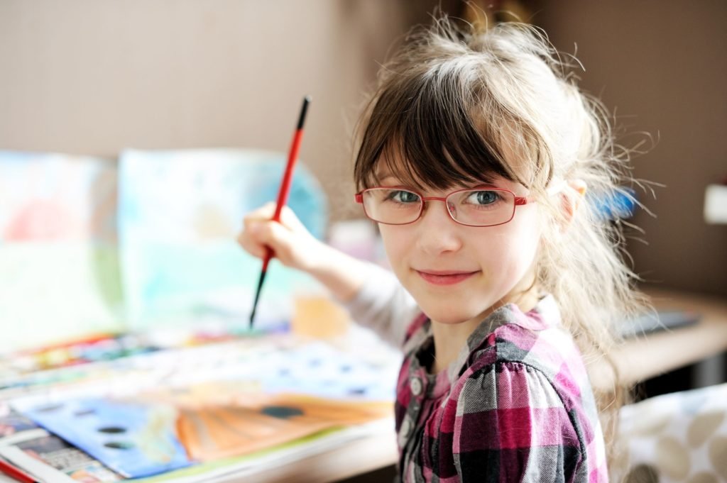 little girl with glasses painting