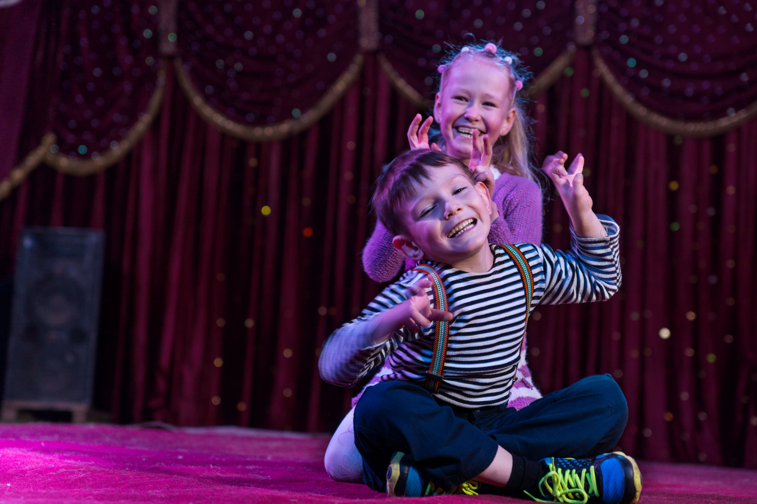Two funny children acting as monsters on stage